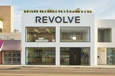 Store design - Revolve clothing, interior, love couch in the window with throw and pillows, minimal and welcoming