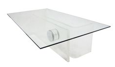 1970S LUCITE COFFEE TABLE  A 1970s Lucite coffee table with a rectangular glass top. The base is comprised of two L-shaped Lucite pieces joined by a chrome cylinder at the center.