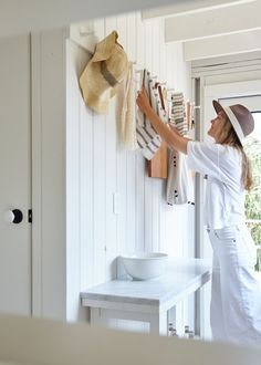 the entryway of this miniature beach cabin is also the kitchen - pegs hold everything from hats to cutting boards | via coco kelley