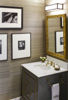 Powder room with taupe grasscloth wallpaper, black and white photos, gray lacquered vanity, brass mirror