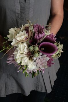 Bouquet of calla lilies, freesia, succulents, mossy branches, and living tillandsia air plants. From www.tendingtoit.com.