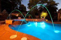 Free form pool with fountains, spa, and colorful lighting