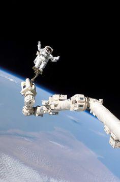 NASA 1984 L'astronaute Stephen K. Robinson évolue dans le vide spatial attaché au bras robotisé Canadarm2 de la station spatial internationale pendant la mission de la navette spatiale Discovery le 3 août 2005. Tirage chromogénique postérieur. 30,5 x 20 cm.