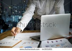 Startup business people using laptop and summery business chart to analyze marketing situation. Working people doing overtime at night in…