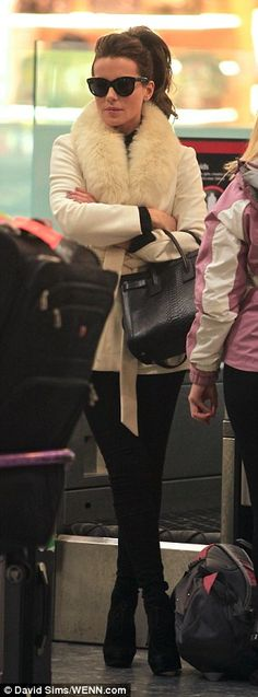 Arm candy: The actress paraded her designer handbag as she made her way onto the flight