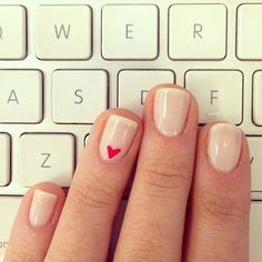 Simple heart nail polish on the ring finger of a plain nude manicure in front of a keyboard.