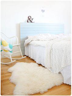 Blue headboard, white bedding, sheepskin rug. <3