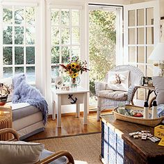 Relaxing Sunroom - A sea grass rug, wicker and wood furniture, and plenty of streaming light from the French doors fill this sunroom.