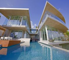 A daytime view of the length of the pool from near the end of it. The oversized windows that cover this side of the home take full advantage of the gorgeous cliff-top view.