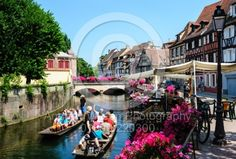 Tourists sightseeing in a punt in the area known as Little Venice in Colmar, Alsace, France