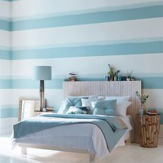 Dormitorio con papel pintado a rayas en azul de Harlequin - Villalba Interiorismo