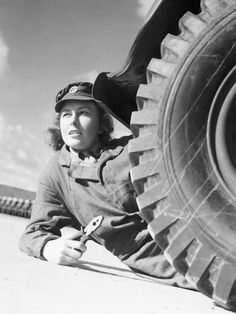 A member of the ATS, pliers in hand, lies on the ground next to the wheel of a lorry or truck, as she prepares to change the wheel as part of her training. It is possible that this photograph was taken at the training centre at Camberley, Surrey ~