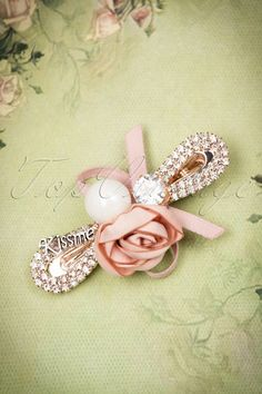 This50s Kiss Me I'm So Cute Hair Clip is super cute!  This clip is soooo cute, you would want to kiss it... ohh wait a minute, it has'Kiss me' written on it! The adorable old pink rose and bow, the lovely faux pearl and the shiny faux diamonds give it a cuteness overload ;-)Made from a rose gold toned metal and finished off with a firm clip at the back.This beauty definitely deserves a place in your jewelry box!   Rose gold toned ...