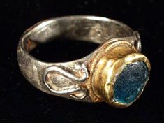 ROMAN GOLD AND SILVER RING           IV c. A.D.  Ellipsoid hoop, made of a flat silver band, slightly rounded on the outside,   progressively widening  towards the rounded bezel. High gold shield  with twisted wire boarder, blue glass inlay in box setting . Ω-shaped beaded wire is soldered to each shoulder.