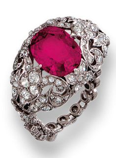 RUBY AND DIAMOND RING, EARLY 20TH CENTURY  Centring on a cushion-shaped ruby weighing 1.97 carats, the pierced scrollwork bezel, gallery and shoulders highlighted with circular-, single- and rose-cut diamonds, on an articulated band collet-set with a line of single-cut stones, size 54 ½.
