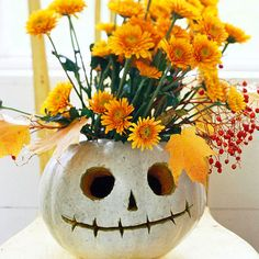 Floral Jack-o'-Lantern Halloween Centerpiece A smiling jack-o'-lantern becomes the perfect Halloween vase when you place a container of water and flowers inside. A simple carving (or scraping) that forgoes the typical wide mouth will help the inside container stay hidden. Use a white pumpkin and orange flowers for extra pop.