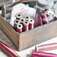 Old French wooden spools of thread in pretty shades of fuchsia, raspberry red, or pink