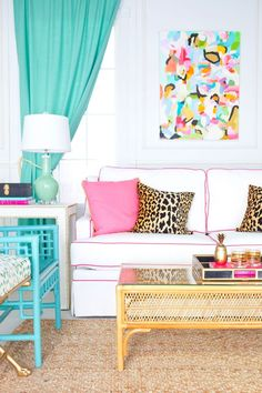 Colorful living room with white sofa (with pink piping) and turquoise bamboo chairs plus matching turquoise drapes. Love the mix of pillows with leopard and hit pink. // In the Buff & Blue