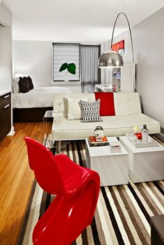Inspiration...Notice that ghost side table right next to the sofa bed? It can be rolled to go underneath the sofa and serve as a small table/laptop tray. LOVE the stripe rug