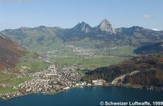 Mythen Mountains with Ingenbohl-Brunnen direct by the Lake Lucerne and  Schwyz - the capital of Canton Schwyz in the middle of the open valley. The mountains left of the Small Mythen is Haggenegg and the mountain right of the Big Mythen is Holzegg and the bigger one more right is Rothenfluh