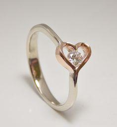 romantický zásnubný prsteň z bieleho a červeného 14 kt zlata. Uprostred srdca žiari diamant s okrúhlym briliantovým brusom 0,16 ct, čistote SI1, farbe F