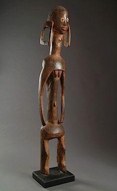 Lot 186  GRANDE STATUE MUMUYE, NIGERIA représentant un personnage féminin, les jambes allongées, le torse cylindrique et les bras enveloppant, des petits seins indiqués sous le sternum, le long cou supportant une grosse tête ronde, les lobes des oreilles distendus Hauteur : 124 cm    Collection Pierre Parat, Paris, vers 1970  Art tribal - Vente N° 1473 - Lot N° 186 | Artcurial