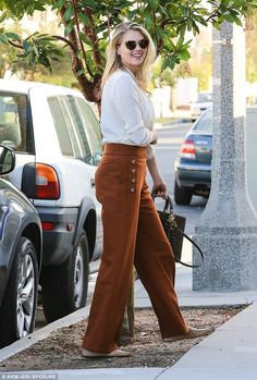 All class: The swimsuit model-turned-actress was all smiles as she showed off her outfit which consisted of a cream blouse and red ochre trousers with beige moccasins