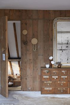 The couple clad one whole wall in the master bedroom with salvaged floorboards to section off the ensuite. The panelling cleverly conceals the door leading to the bathroom. One of a series of three wooden wall hooks (from muuto.com) acts as a handle for the door. The vintage chemist's drawer unit and French mirror are both vintage finds
