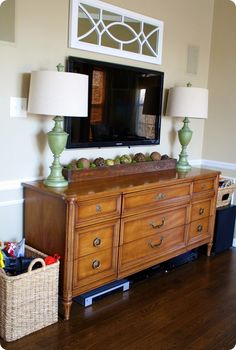 Dresser as a TV stand. Store the components underneath, and toys and DVDs inside. I especially like this look with the lamps and the planter box underneath.