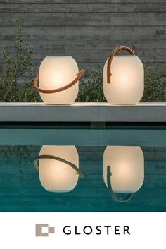 Add a warm glow to your outdoor living space with the beautifully designed Gloster Ambient Cocoon outdoor light. This cocoon-style light has a teak frame and rechargeable LED light with a variable setting remote control. The polypropylene shade provides o Outdoor Table Lamps, Outdoor Sconce Lighting, Deck Table, Outdoor Light Fixtures, Lighting Ideas, Gloster Outdoor Furniture, Outdoor Living Furniture, Solar Patio Lights, Led Garden Lights
