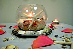Fish bowl #centerpiece layered with sand, & #seashells. Two #starfish sit adjacent to one another surrounding the soft elegant glow of a tealight. A Piccanti Creation.