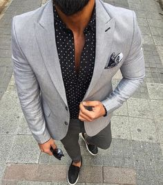 Opt for a grey blazer jacket and charcoal casual trousers if you're going for a neat, stylish look. Black leather slip-on sneakers will add a new dimension to an otherwise classic look. Shop this look on Lookastic: https://lookastic.com/men/looks/blazer-long-sleeve-shirt-chinos/20931 — Grey Blazer — Black Print Long Sleeve Shirt — Black Paisley Pocket Square — Charcoal Chinos — Black Leather Slip-on Sneakers