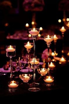 Varying heights and shapes of Candles on table. Placements of different heights adds to the ambiance.