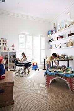 Przestronny pokój z dużymi oknami i ozdobnymi sztukateriami przy suficie stanowi centrum kreatywnej zabawy dla dzieci. Każda z zabawek ma swoje miejsce na jednej z półek ściennych, regale, dużym industrialnym stole lub w skrzyni-schowku. Dla komfortu dzieci podłogę wyłożono miękką wykładziną dywanową o wyrazistej strukturze.