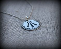 This is a sterling silver, hand stamped Awen symbol. Comes on a sterling silver box chain.  Awen, a Welsh word, describes the spark of creative or divine inspiration or illumination. Awen is what sparks an idea and gives it form. The ancient bards drew upon Awen in the process of composing their beautiful stories and music. Measures 3/4 inch across.  Thin chain is .85mm (The first two photos are on this one) Thick chain is 1.1mm  You have two choices of thickness of chain as shown in the…