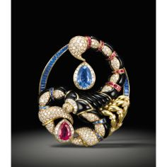 MAUBOUSSIN, PARIS THE EMPEROR SCORPION A FINE AND VERY RARE YELLOW GOLD, DIAMOND, SAPPHIRE, RUBY, EMERALD, MOTHER-OF-PEARL, LAPIS LAZULI, ONYX AND ROCK CRYSTAL MANTEL CLOCK AND BROOCH CIRCA 1985