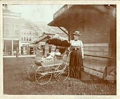 A young mother with her baby in a fancy wicker carriage poses on the north side of the Fremont, Elkhorn and Missouri Valley depot in Deadwood. Behind her is the McCracken Grocery Store, where the Adams Museum would later be built and an unknown business in what was the Rosengarder's House where the Federal Building would be built.