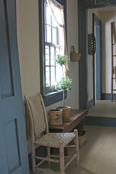 Mudroom Doors , Window, and Woodwork Trim in Blue Paint with a Simple Potted Topiary Set on an Antique Bench.