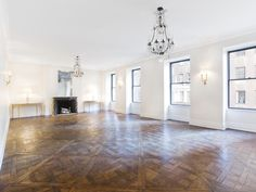 Empty living room in a multi million dollar real estate listing new york city apartment coop.  Parquet wood floors. Crystal chandeliers.