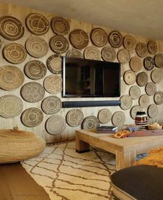 The wall in this family room is paneled with African wedding trousseau baskets.
