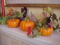 A simple way to decorate a mantel - 3 pumpkins and a vine.