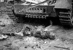 The stillburning corpse of a soldier can be seen in front of a tank near Hemmerden Germany during the Allied push to the Rhine World War II The...