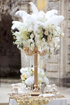 tall centerpiece inspiration. White & cream floral with feathers at top and hanging crystal strands in tall glass slim vase