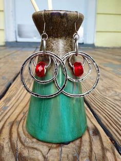 These simple intertwined vintage piece earrings are handmade to encourage freedom of movement. With antique patina silver hoops and red center accent beads.