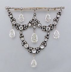 A SUPERB ANTIQUE DIAMOND CORSAGE BROOCH   In the form of a festoon suspending six pear-shaped diamond drops weighing from top left 3.56, 3.03, 3.36, 4.41, 3.16 and 2.48 carats, mounted in platinum, from a detachable brooch fitting, mounted in silver and gold, festoon circa 1880.Consuelo, Dowager Duchess of Manchester (1859-1909).