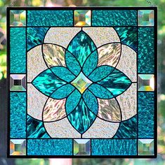 Deep aqua blue and clear textured stained glass is used in this original design hanging stained glass panel. Glass bevels have been added for a stunning effect. This panel measures nearly 13 tall by wide, actually 12 7/8 inches tall by 12 3/4 wide, nearly 33 cm tall by 32.5 cm wide. The center is a clear glass star shaped bevel surrounded by deep, rich textured aqua blue wavy Waterglass and clear Waterglass. Waterglass has a light wavy texture resembling water on a lakes surface....