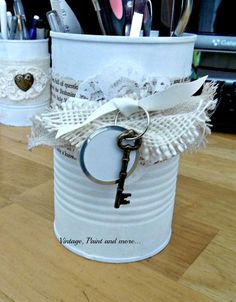 recycled and decorated tin cans, crafts, repurposing upcycling, After painting them I decorated them by gluing on all sorts of bits and pieces This one has a bit of book page wrapped around it then a small medallion of lace with burlap and ribbon added Lastly a key and label