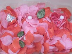 Valentine Day Sensory Bin - Uses rose petals, heart trinket boxes, and looks like clay or wooden leaf shapes.