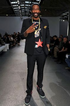 NBA-star Amare Stoudemire wearing a noir tux w/ Givenchy F/W 2012 Apache print t-shirt and Nike Air Yeezy 2 solar-red sneakers at Givenchy Menswear S/S 2013 fashion show during Paris Fashion Week