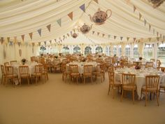 Hanging buntings everywhere is a unique and affordable way to bring interest and color to the ceiling of your tent or reception hall.